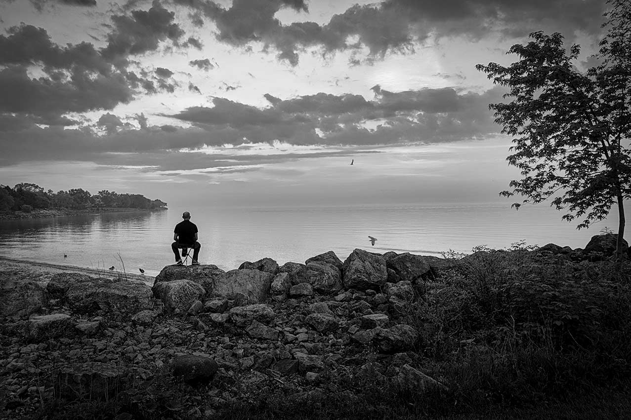 Man Sitting by the lake watching sunset
